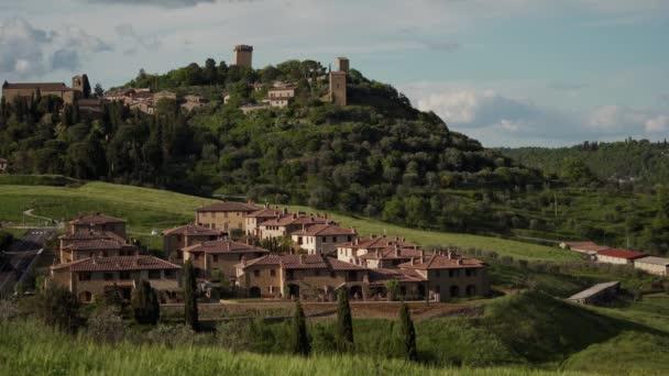 Toskánská krajina s loukami, italskou vesnicí a středověkým městem Monticchiello