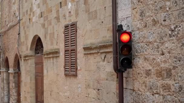 Traffic light on old Italian city burns red. Prohibiting traffic light stop