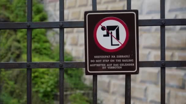 Kreatives Schild, das das Klettern über Zaun verbietet. Skizzenhafter Mann hängt am Geländer