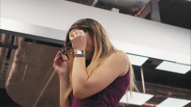 Mladá žena se snaží na stylové módní brýle v úložišti