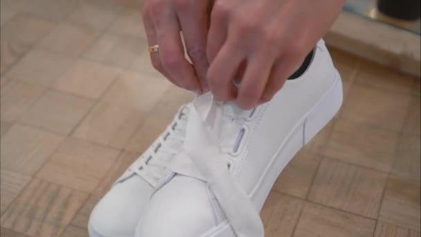 Mladá žena váže její tkaničky na Bílé tenisky v úložišti. Detail