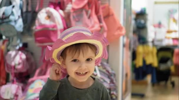 19a77bf2912 Little boy dresses hat in shop and smiles. Portrait. Kids shopping– stock  footage