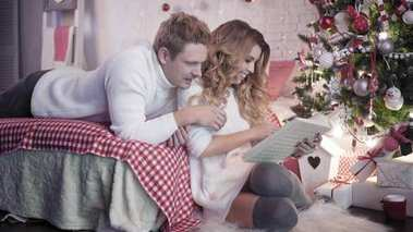 Young beautiful couple looking at photo album near Christmas tree