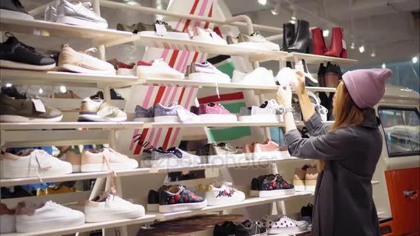 Minsk, Bělorusko - 10 října 2017. Vnitřní Pull a medvěd maloobchodní prodejny v Minsku. Mladá bokovky ženské v módní brýle zvolí nové tenisky v úložišti