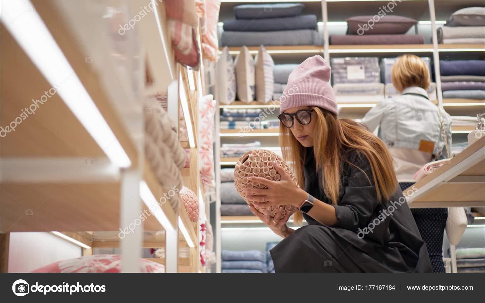 Minsk, Bielorrusia 10 de octubre de 2017. Interior Zara Home Tienda en Minsk. Una mujer joven inconformista elige accesorios Inicio la tienda. Ir de compras
