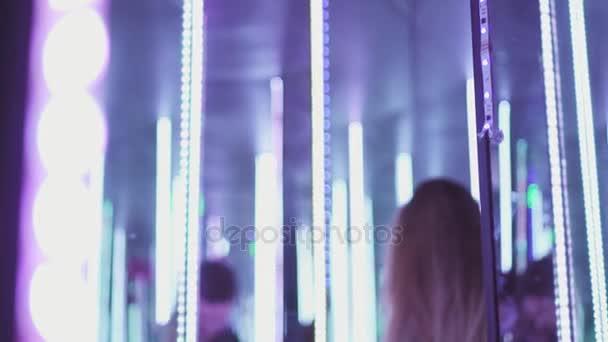Bokovky žena ve stylové brýle stojí v zářivě barevných světel při pohledu na fotoaparát a mrkl