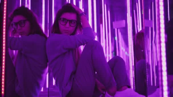 Bederní žena ve stylové brýle sedí v zářivě barevných světel a vypadá na kameru