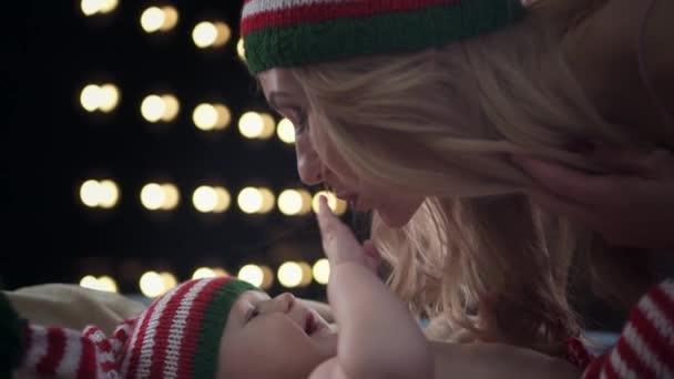 Krásná blondýna matka v pruhované čepici dává svého synka Polibky a vezměte ho. Dítě se usmívá a jemně hladil po tváři matky