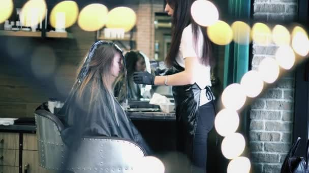 Hair dresser applies coloring dye on womans long hair in foil. Young hipster girl sitting in chair in hair saloon and dyes her hair. Twinkle lights