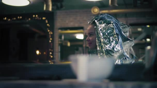 Happy woman is sitting in chair in hair salon and smiling. Her head is full covered with hair dye. Strands of hair in foil. Profile angle. Slow mo.
