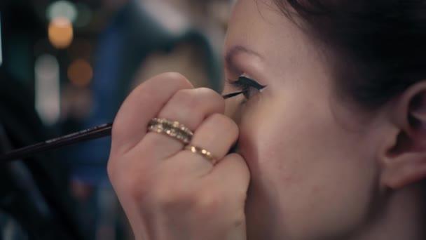 Closeup vizážista je dávat make-up na oči modely v salonu krásy. Profesionální oční make-up, profil