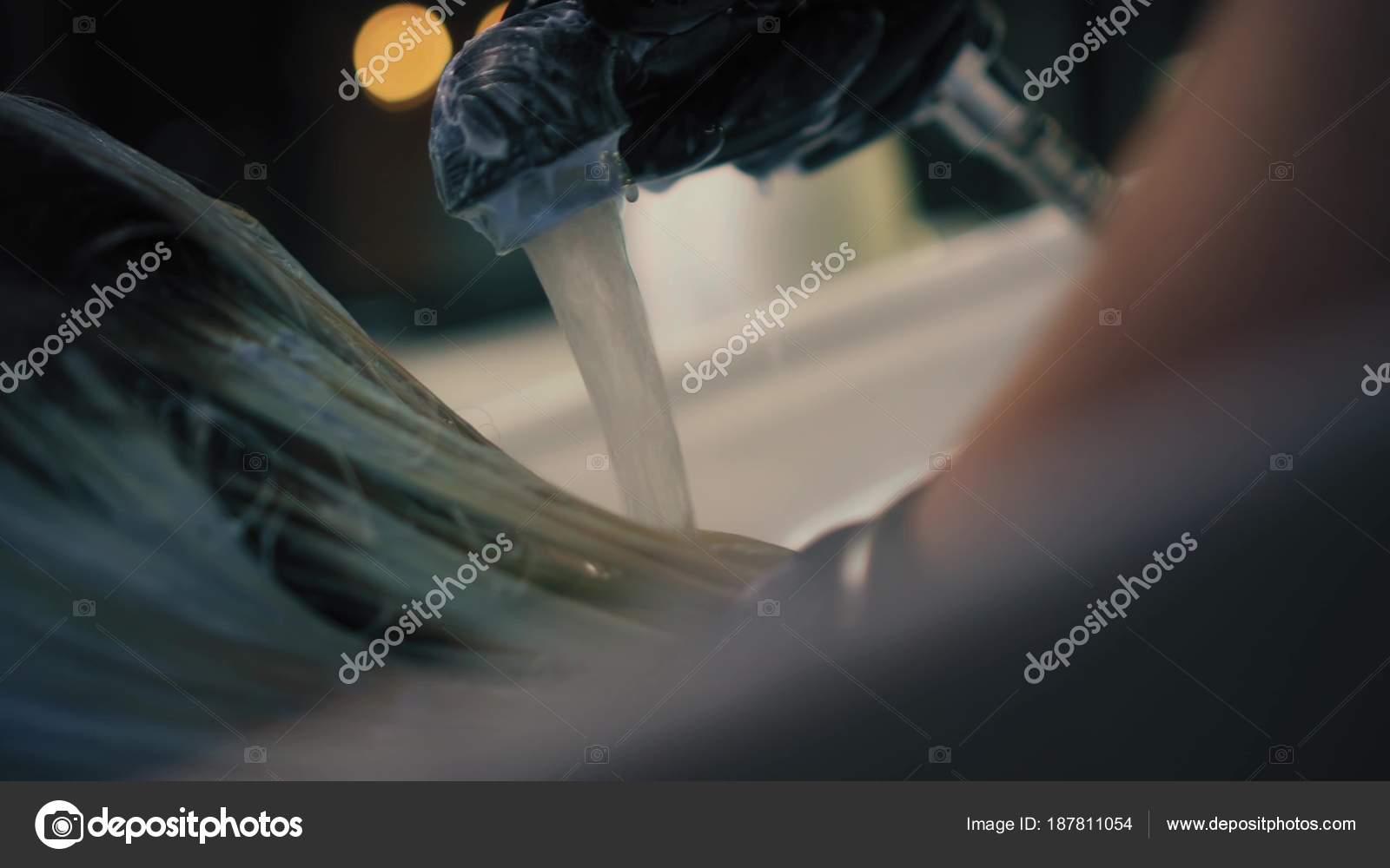 Peluquería en guantes negros lava cuidadosamente el tinte de pelo de ...