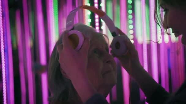 Fiatal női segít idős nő viseljen olyan fejhallgatót. Felnőtt hölgy is hallgat  zenét 056d432614