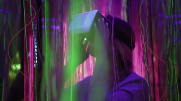 Krásné bokové žena stojí v neony, staví na virtuální realita brýle, usmíval se a překvapující. Žena používá vr brýle. Pomalé mo