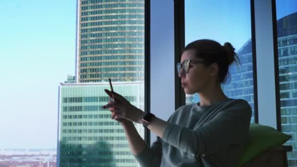 Bokovky žena v brýlích používá aplikace na mobilním telefonu a fotografování výhledem na mrakodrapy. Žena s smartphone