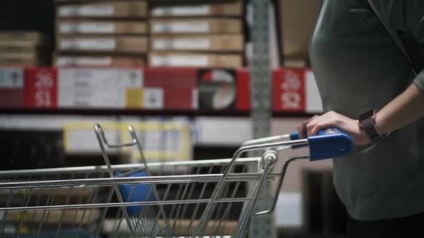 Closeup view on woman in a store with a shopping trolley. Hands are on a shopping cart. Woman is making shopping