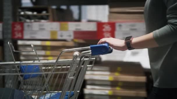žena dělá nákupy v obchodě. Ženské ruce jízdy nákupní vozík v železářství
