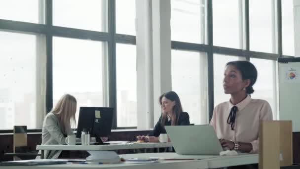 Žena multietnický manažer pracující v kanceláři s notebookem a s úsměvem. V pozadí komunikují kolegyně. Spolupracuju. Kancelářský život. Obchodní prostor