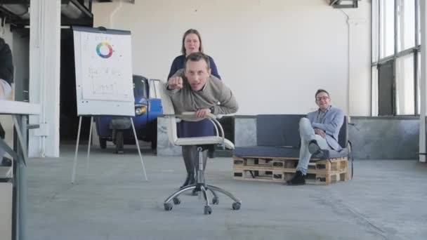 fice chair race. A young businessman rides on a chair in the office, like a winner. A female colleague rolls it. Colleagues have fun. Corporate party. Office life. Coworking.