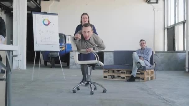 Fice chair race. Mladý podnikatel jezdí na židli v kanceláři, jako vítěz. Dělá to kolegyně. Kolegové se baví. Firemní večírek. Kancelářský život. Spolupráce.