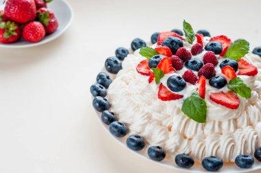 Pavlova meringue cake with cream and berries isolated on white background