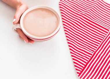 Top view of hot coffee with milk top view on a striped napkin on wood table background