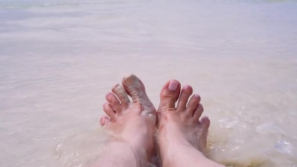 Nohy mladé dívky na pláži ve vodě. Průhledná voda, bílý písek