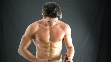 Svalnatý mladý muž použití olej do jeho kůže