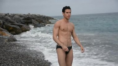 svalnatý muž v trenkách pěšky podél mořského pobřeží