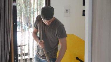 mladý muž pečlivě zametal podlahu