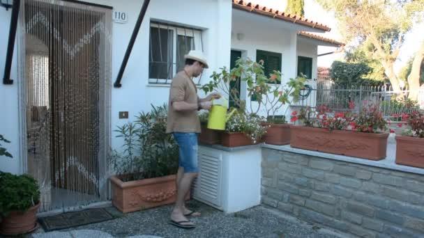 mladý muž zalévání rostlin na terase