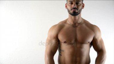Muscular bodybuilder by white wall