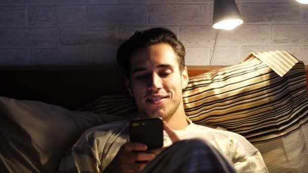 Csinos, fiatal férfi az ágyban gépelés-on sejt telefon