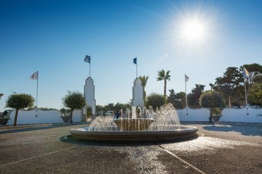 People behind water fountain in Kalithea (Rhodes, Greece)