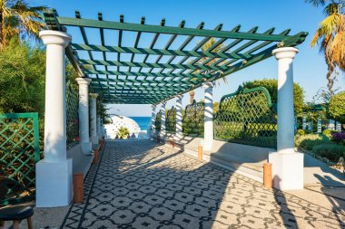 People on main stairways with pergola in Kalithea (Rhodes, Greece)