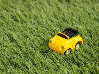 A yellow toy car park on green grass field.