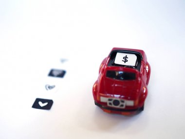 Sim card tray and small paper simulated as a SIM card on a red toy car with white background.  Dollar, wifi and heart symbol on paper sim cards.