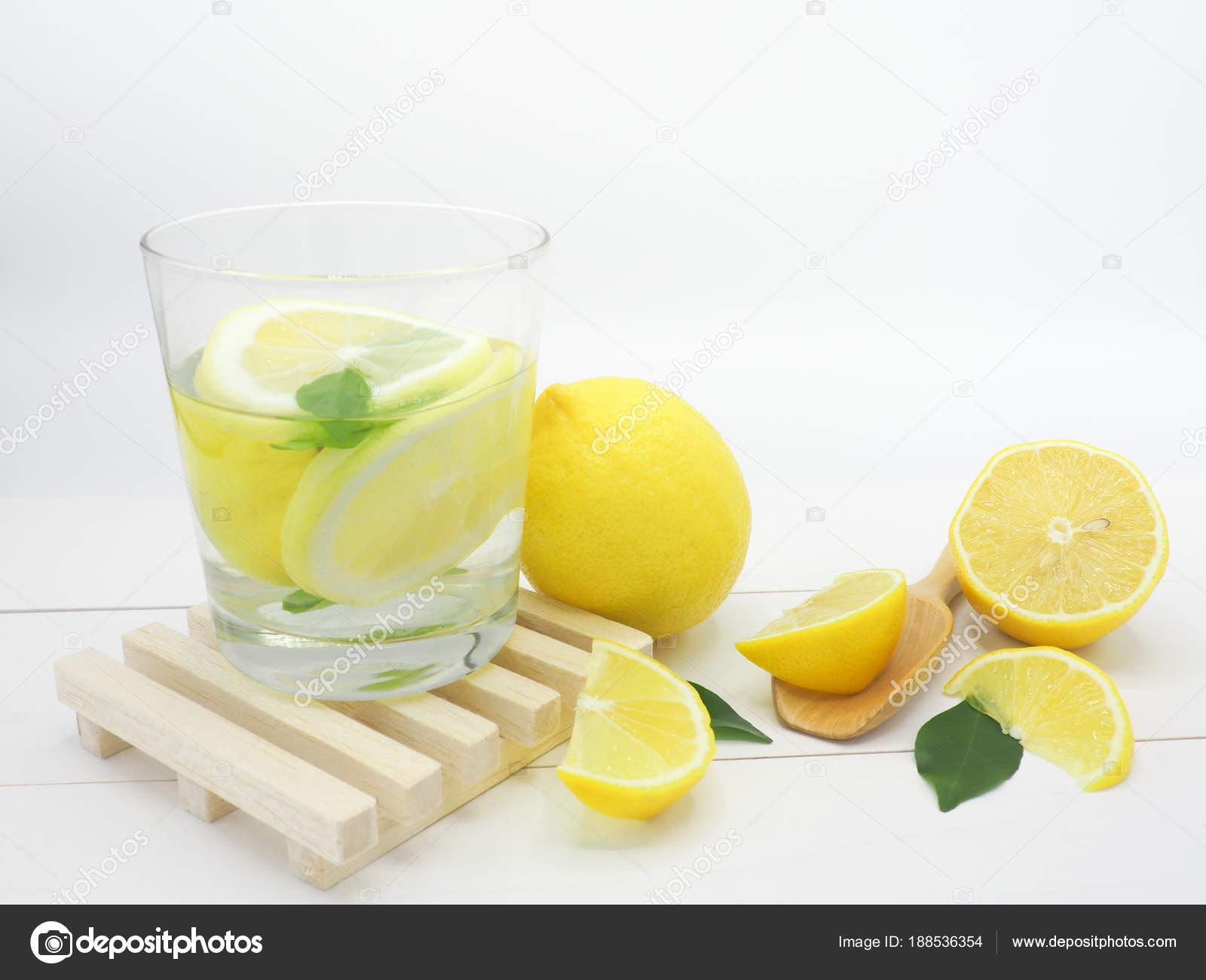 fresh lemon in water and lemon slice on white wood background