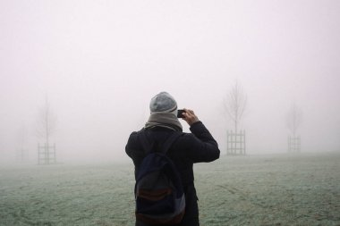 Man taking phone pictures of a park in fog