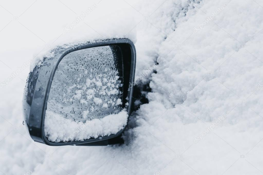 Side mirror on a car completely covered in snow, selective focus