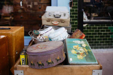 LONDON, UK - MARCH 21, 2016: Stack of vintage suitcases and various vintage items in Chatsworth Road Market. The market has a long heritage and is located on one of London's longest high streets. stock vector