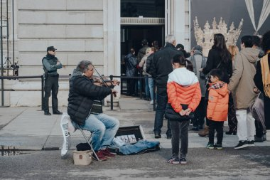 Madrid, Spain - January 26, 2020: Girl wearing a face mask listening to street musician while in queue to buy ticket to Madrid Palace, is the official residence of the Spanish royal family.