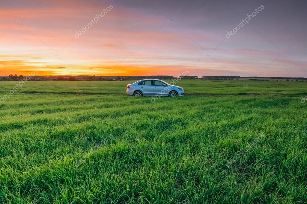 Volkswagen Polo Vento in against the sunset in a summer rural fi