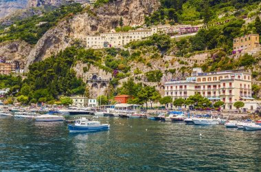 Harbor with boats and yachts of Amalfi village  colorful houses, located on the rock, Amalfi coast, Sorrento, Italy.
