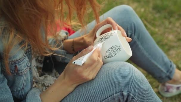 Közeli kép a rajz a minta fehér kupa női kéz. Lány festékek dísz este ül a fűben.