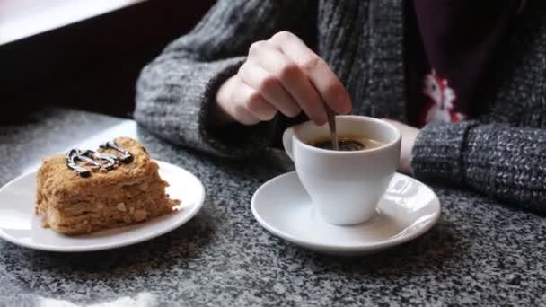A lány moccan cukor, kávé a fehér csészében. Női kéz, egy csésze presszókávé americano.
