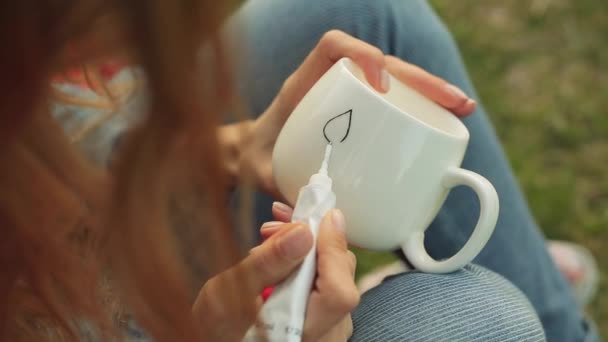 Közeli kép a lányok kezében egy minta támaszkodva a fehér kupa. Lány festékek dísz este ül a fűben.
