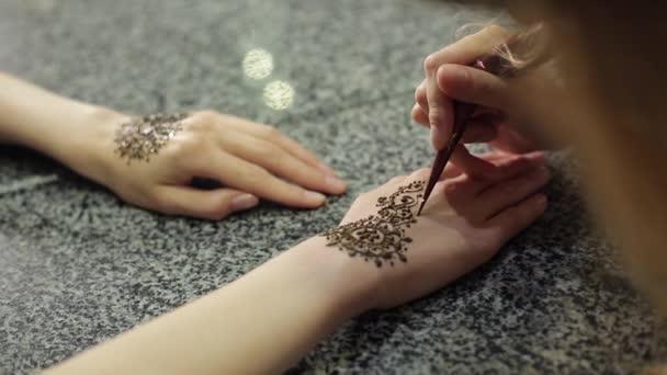 Nő, ami virág mehendi a henna asztalon egy kinyújtott.