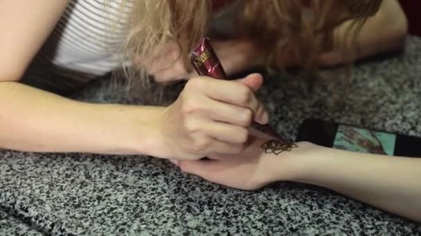 Nő, ami virág mehendi a henna asztalon egy kinyújtott
