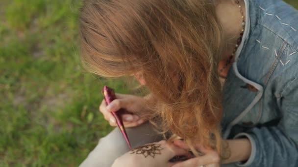 Fiatal nő így virágos mehendi egy leosztást használ hennát.